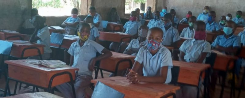 A class of children seated at desks wearing face masks